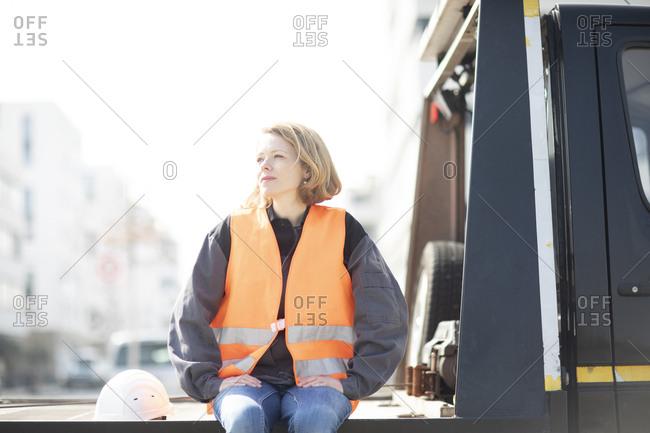 Woman wearing reflective vest sitting on truck platform
