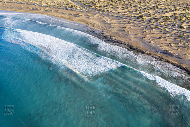 Spain- Canary Islands- Lanzarote- Caleta de Famara- Playa de Famara- waves on sandy beach- aerial view