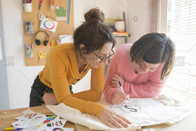 Two women drawing stencils for printing sweatshirts