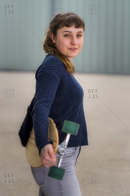 Portrait of smiling young woman with longboard