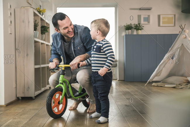Father helping son riding with a balance bicycle at home