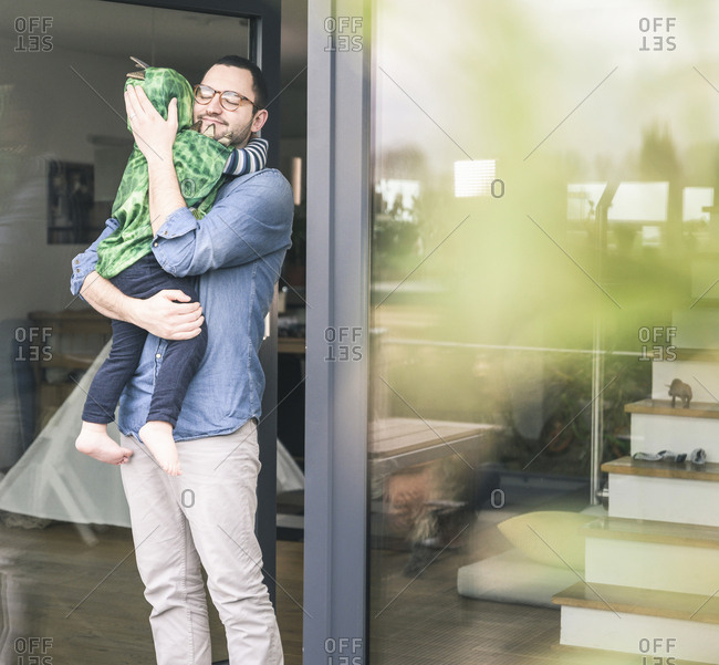 Affectionate father carrying son in a costume at terrace door at home