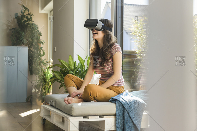 Happy young woman sitting at the window at home wearing VR glasses
