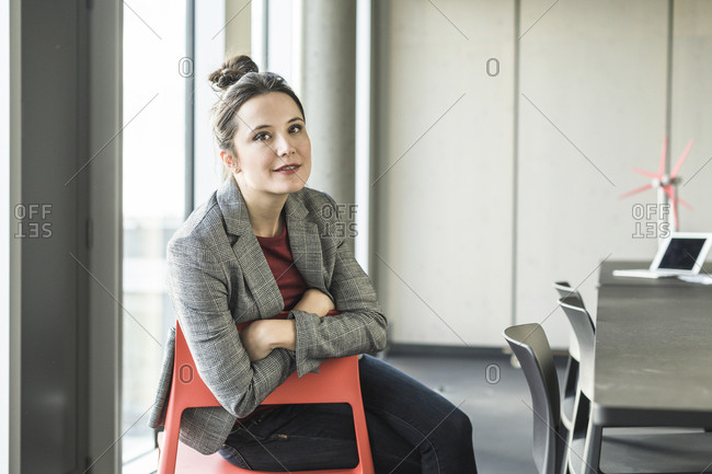 Portrait of smiling businesswoman sitting on chair in office