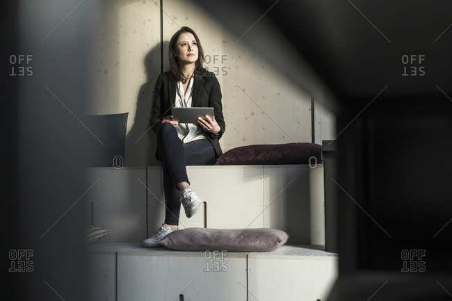 Businesswoman with tablet sitting in lounge area in office