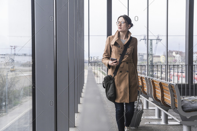 Businesswoman walking with baggage and cell phone
