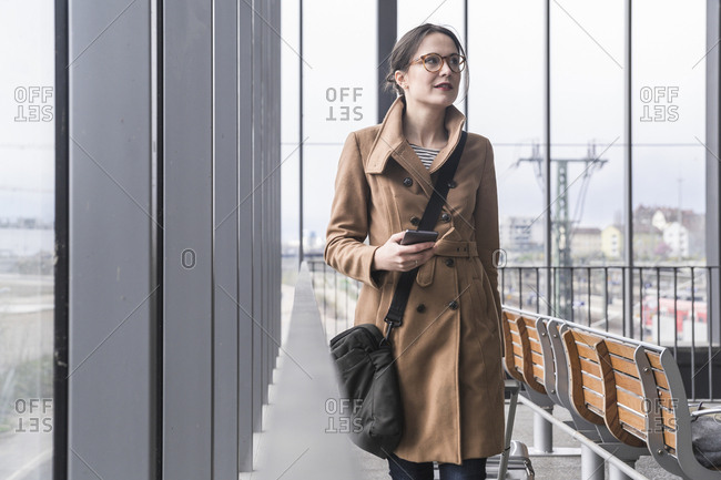 Smiling businesswoman walking with baggage and cell phone