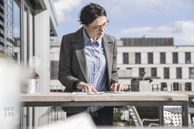 Businesswoman using cell phone on roof terrace