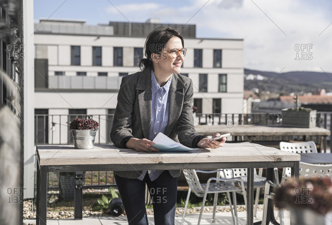 Smiling businesswoman using cell phone on roof terrace
