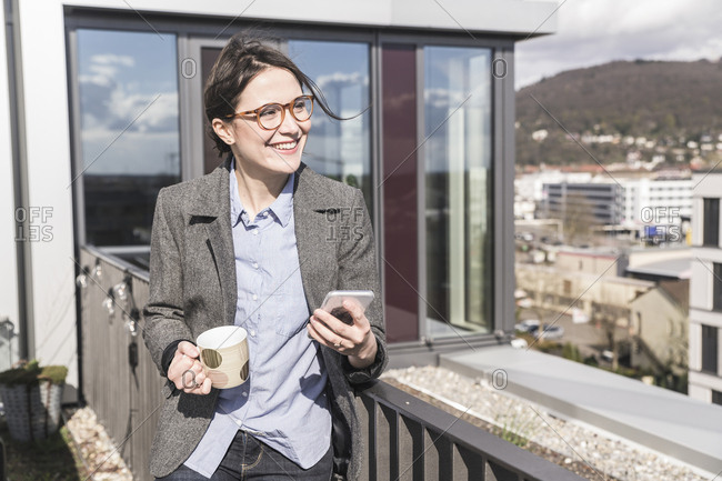 Smiling businesswoman with cell phone and cup of coffee on roof terrace