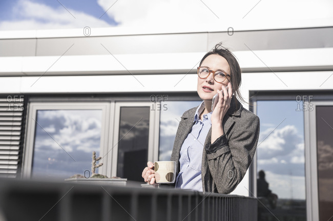 Businesswoman on cell phone on roof terrace
