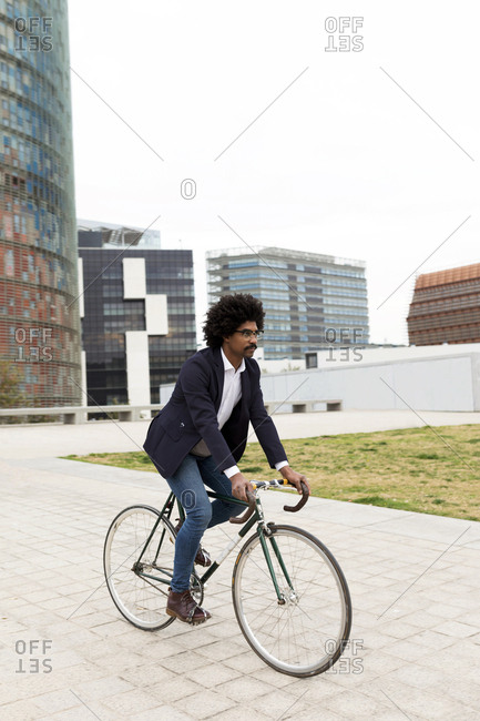 Spain- Barcelona- businessman riding bicycle in the city