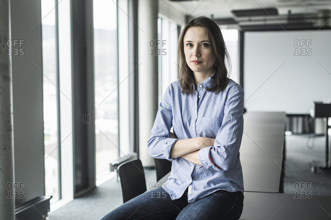 Portrait of serious businesswoman sitting on conference table in office