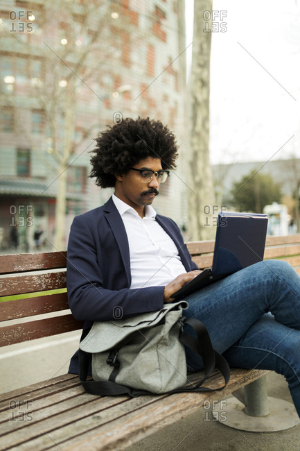 Spain- Barcelona- businessman in the city sitting on bench using laptop