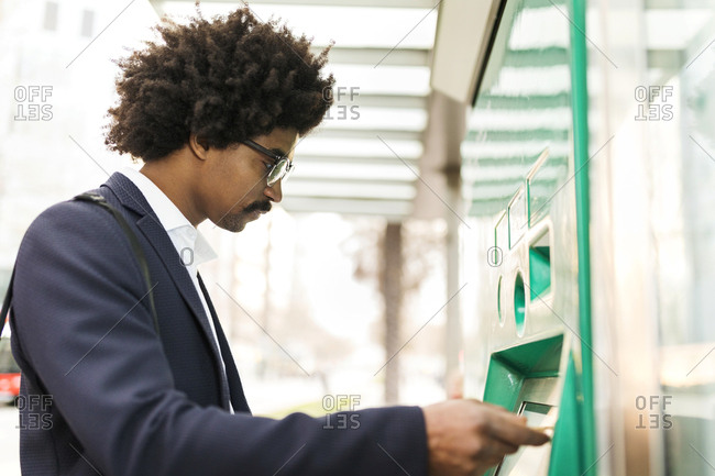 Spain- Barcelona- businessman using ticket machine at tram stop in the city