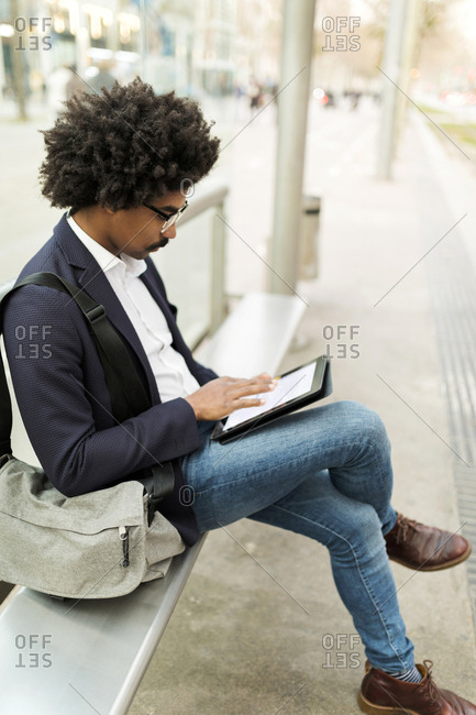 Spain- Barcelona- businessman in the city sitting on bench at a station using tablet