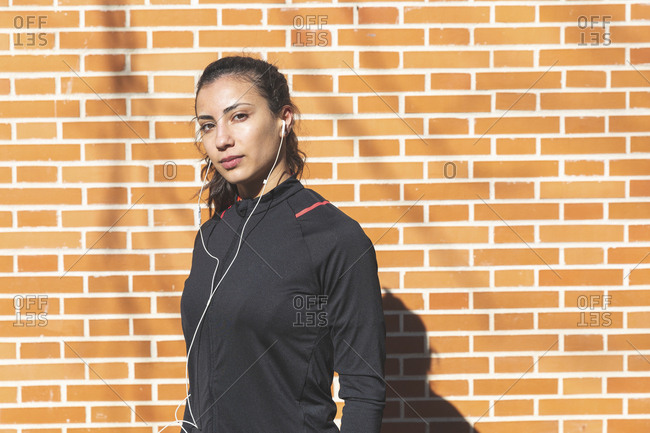 Portrait of sporty young woman with earphones at a brick wall