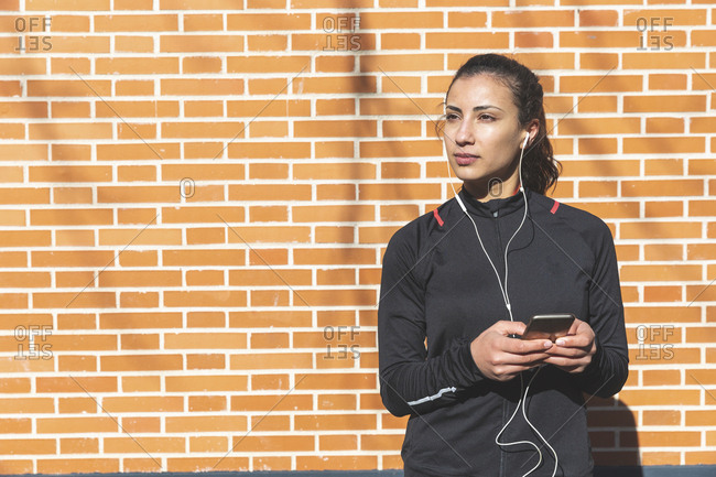 Portrait of sporty young woman with earphones and cell phone at a brick wall