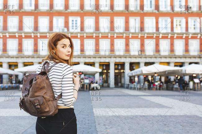 Spain- Madrid- Plaza Mayor- portrait of redheaded young woman with backpack in the city