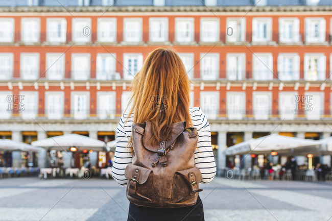 Spain- Madrid- Plaza Mayor- back view of redheaded young woman with backpack in the city