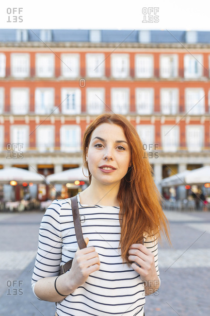 Spain- Madrid- Plaza Mayor- portrait of redheaded young woman with nose piercing