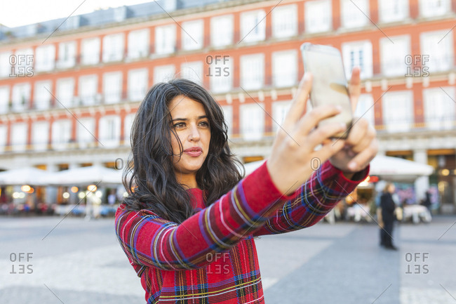 Spain- Madrid- Plaza Mayor- portrait of woman taking selfie with smartphone