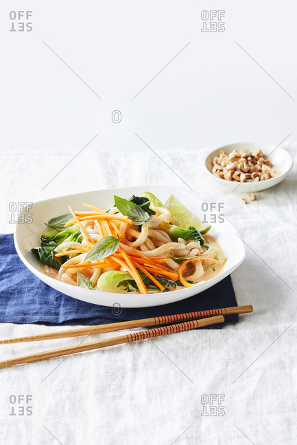 A dish with Shanghai noodles on a blue napkin, set with chopsticks and a ramekin of chopped peanuts.