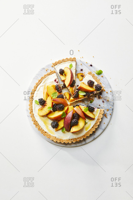Freshly baked tart topped with peaches and blackberries