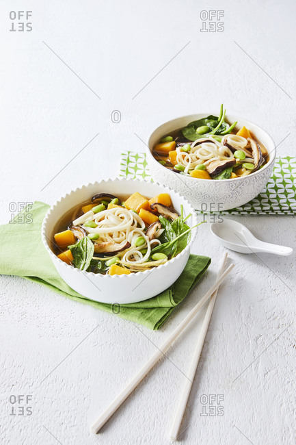 Two bowls of vegetable soba noodles soup on green napkins set with traditional chopstick and soup spoon.