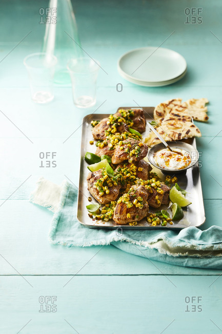 Tray of chicken thighs with corn and lime. Set with sauce and toasted bread. Turquoise background.