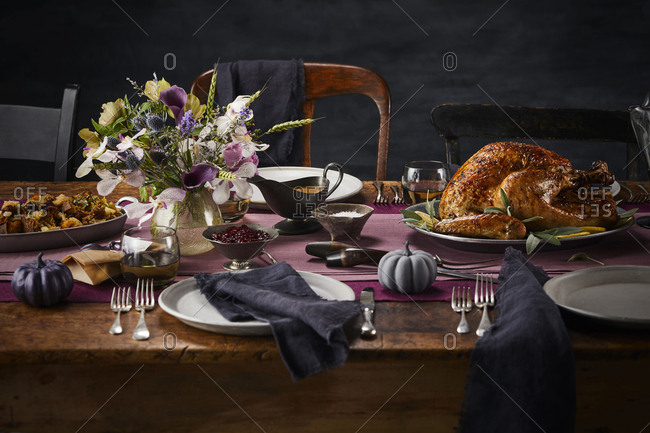 Thanksgiving day feast on a wooden table set with turkey, stuffing and flowers.