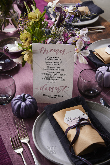 Table setting with menu and name tag on plate.