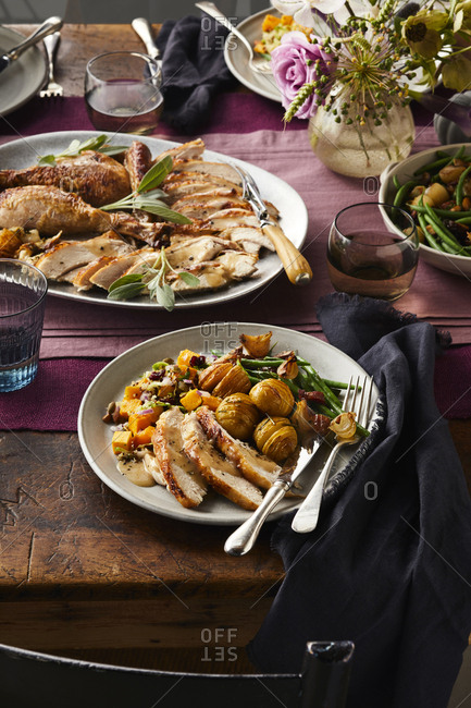 Thanksgiving day plate filled with turkey and vegetables set on a wooden table with silverware and napkins.