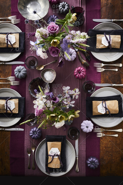 Table set with plates and name tags and purple runner and flowers.