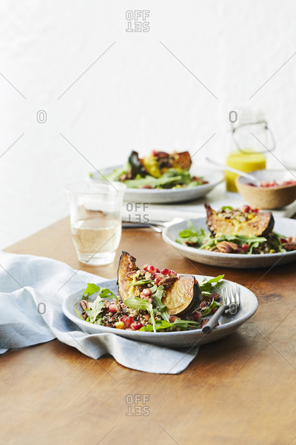 Acorn squash and rainbow quinoa dishes set on a wooden table.