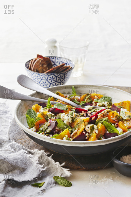 Fresh beet and orange salad in a bowl with serving utensils.