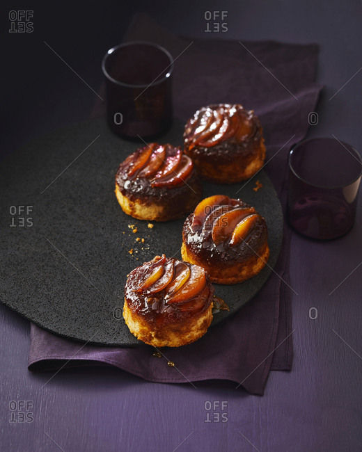 Several small caramel pear spiced cakes, set on a purple background.