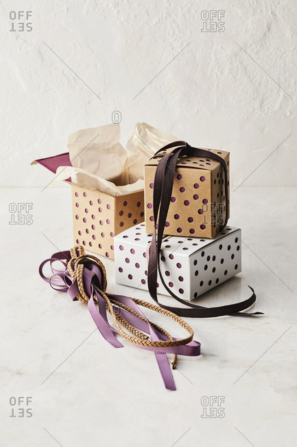 Three decorative boxes with ribbons and ropes stacked on top of each other.