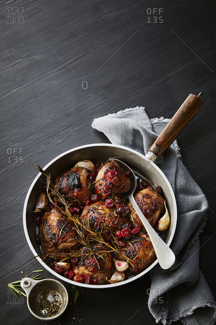 Spoon in a  pan filled with cranberry chicken thighs.