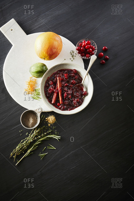 Bowl with cranberry sauce set on a marble cutting board with a lime and orange and assortment of spices.