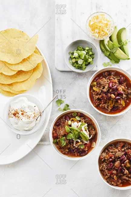 Bowls of beef chili with tortillas sour cream, cheese, green onions and avocados.
