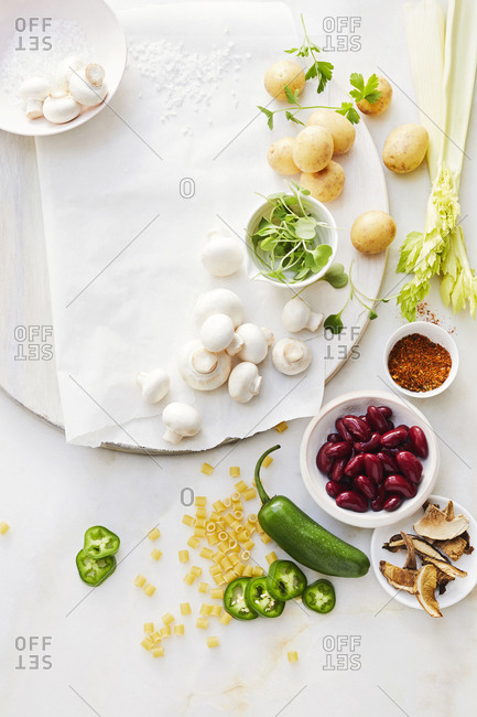 Assortment of different types of vegetables set on a white cutting board on a white table.