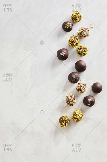 An assortment of chocolate truffles set on a marble counted top.