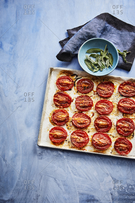 Baked plum tomatoes on a baking sheet with sage leaves