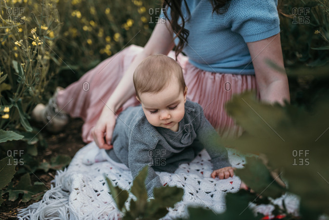 Baby girl crawling on a blanket outdoors