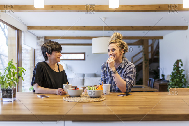 Two beautiful and young women having breakfast at home and having fun