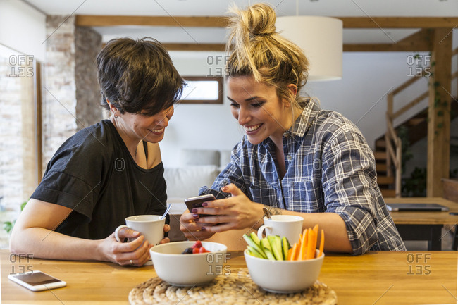 Two beautiful and young women having breakfast at home and having fun, using the smart phone