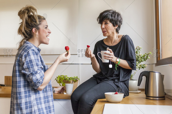 Two beautiful and young women having breakfast at home and having fun, sitting on the kitchen