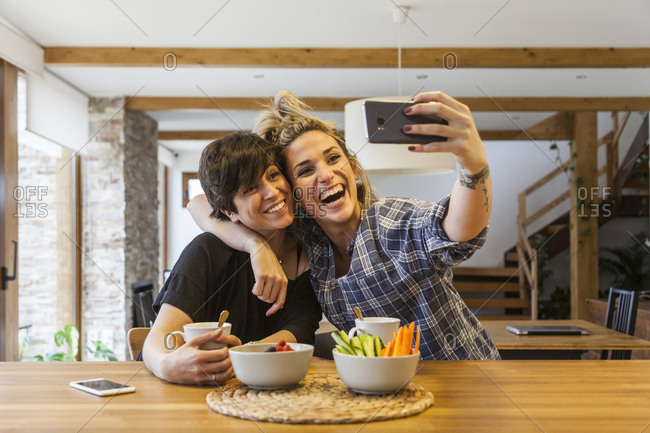 Two beautiful and young women having breakfast at home and having fun, take a auto photo with the smart phone