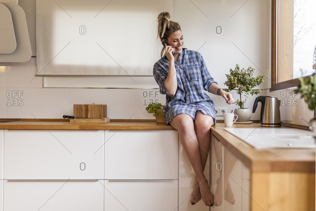 beautiful and young woman having breakfast at home and having fun, sitting on the kitchen and talking on the phone